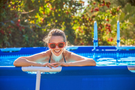 Photo for Fun weekend alfresco. Portrait of happy healthy woman in blue beachwear in the swimming pool in sunglasses - Royalty Free Image