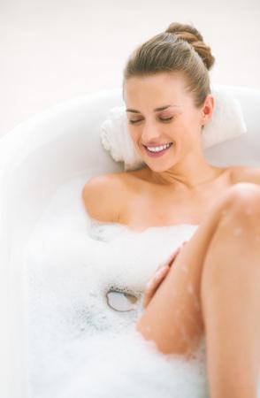 Foto de Smiling young woman laying in bathtub - Imagen libre de derechos