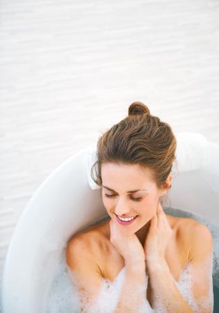 Foto de Portrait of happy young woman laying in bathtub - Imagen libre de derechos