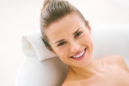 Foto de Portrait of smiling young woman laying in bathtub - Imagen libre de derechos