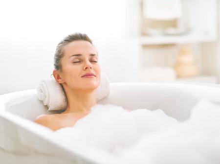 Photo pour Happy young woman relaxing in bathtub - image libre de droit