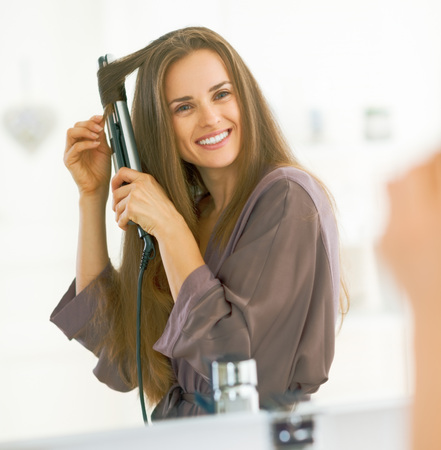 Photo for Smiling woman curling hair with straightener - Royalty Free Image