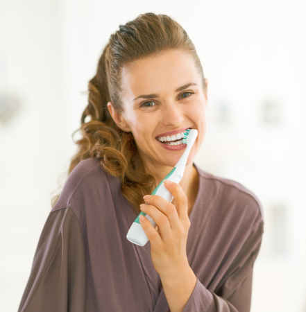 Photo pour Happy young woman brushing teeth in bathroom - image libre de droit