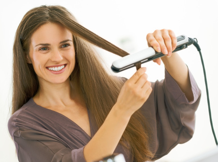 Photo for Happy young woman straightening hair with straightener - Royalty Free Image