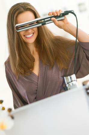 Photo for Happy young woman looking through hair straightener in bathroom - Royalty Free Image