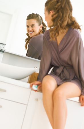 Photo for Happy young woman looking in mirror in bathroom - Royalty Free Image