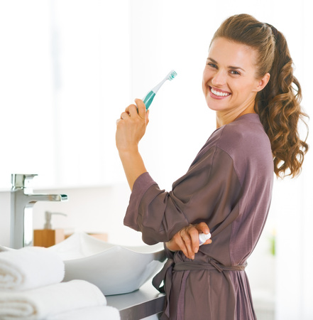 Foto de Portrait of smiling woman with toothbrush in bathroom - Imagen libre de derechos