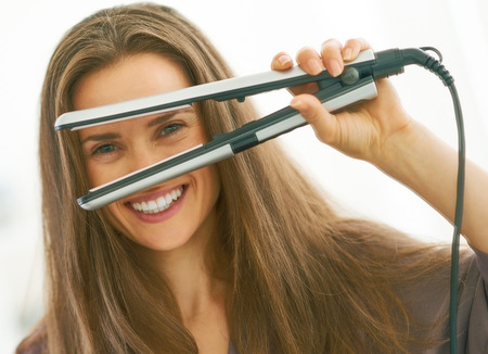 Photo for Happy young woman looking through hair straightener - Royalty Free Image