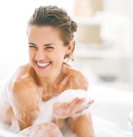 Foto de Portrait of happy young woman playing with foam in bathtub - Imagen libre de derechos