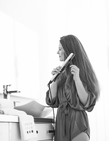Photo for Young woman using hair straightener in bathroom - Royalty Free Image