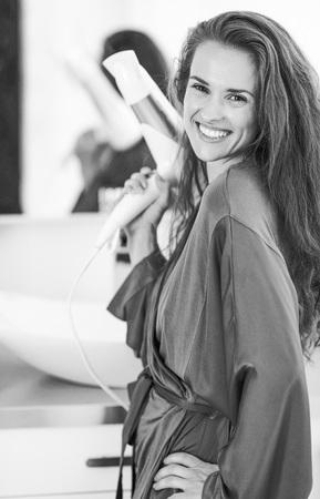 Foto de Portrait of smiling young woman with blow dryer in bathroom - Imagen libre de derechos