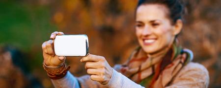 Photo for Closeup on young woman in autumn evening outdoors taking photo with cell phone - Royalty Free Image