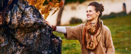 Photo for Portrait of happy young woman standing in autumn park in evening - Royalty Free Image