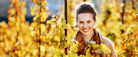 Photo for Portrait of happy young woman standing in autumn vineyard - Royalty Free Image