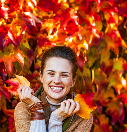 Photo for Portrait of smiling young woman in front of autumn foliage - Royalty Free Image