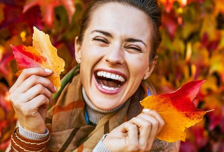 Photo for Portrait of happy young woman with leafs in front of foliage - Royalty Free Image