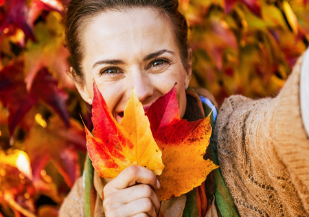 Photo for Happy young woman hiding behind leaf while making selfie in front of autumn foliage - Royalty Free Image