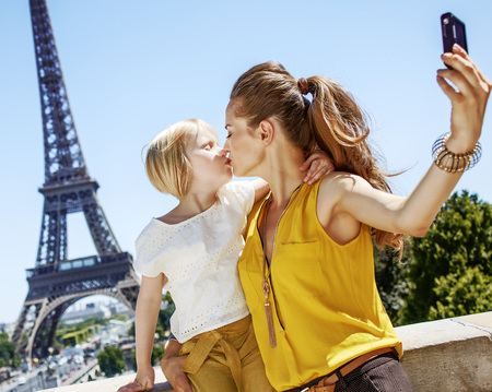 Foto de Having fun time near the world famous landmark in Paris. mother and daughter tourists taking selfie with digital camera and kissing in Paris, France - Imagen libre de derechos