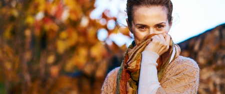 Photo for Young woman hiding in scarf in autumn evening - Royalty Free Image