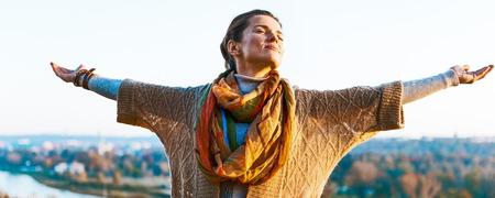 Foto de Happy young woman in autumn outdoors in evening rejoicing - Imagen libre de derechos