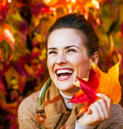 Photo for Portrait of smiling young woman with autumn leafs in front of foliage - Royalty Free Image