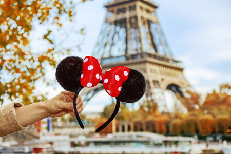 Photo pour Perfect autumn holidays in Disneyland and Paris. Closeup on Minnie Mouse Ears in female hand on embankment near Eiffel tower in Paris, France - image libre de droit