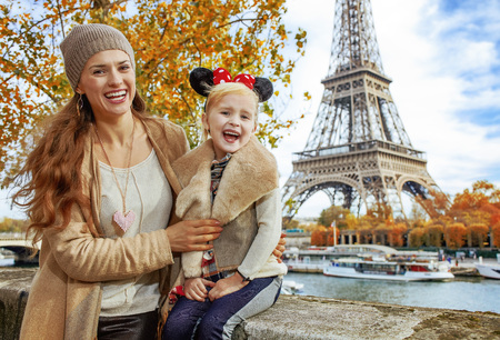 Foto de Perfect autumn holidays in Disneyland and Paris. Portrait of smiling tourists mother and daughter in Minnie Mouse Ears on embankment near Eiffel tower in Paris, France sitting on the parapet - Imagen libre de derechos