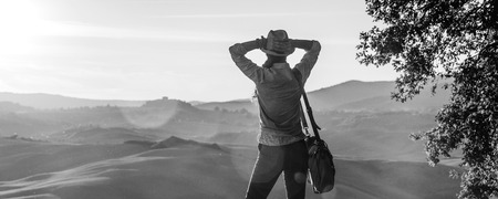Photo for Discovering magical views of Tuscany. Seen from behind relaxed adventure woman hiker in hat with bag enjoying sunset in Tuscany - Royalty Free Image