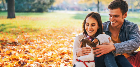 Foto de Portrait of happy young couple sitting outdoors in autumn park and playing with dogs - Imagen libre de derechos