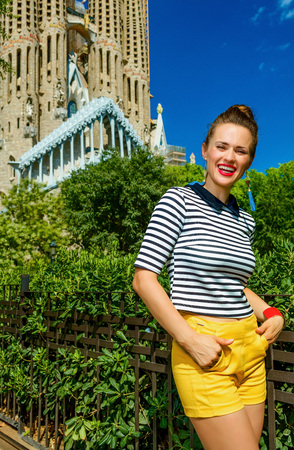 Foto de Barcelona - July, 10, 2017: Portrait of smiling trendy tourist woman in yellow shorts and stripy shirt in the front of Sagrada Familia in Barcelona, Spain - Imagen libre de derechos