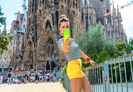 Foto de Barcelona - July, 10, 2017: young tourist woman in yellow shorts and stripy shirt in the front of Sagrada Familia in Barcelona, Spain with mobile phone taking selfie - Imagen libre de derechos