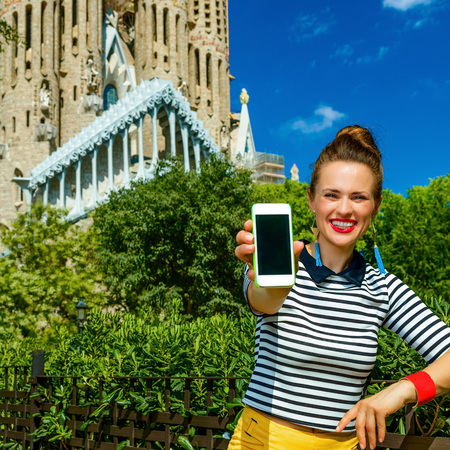 Foto de Barcelona - July, 10, 2017: elegant traveller woman in yellow shorts and stripy shirt against Sagrada Familia in Barcelona, Spain showing smartphone blank screen - Imagen libre de derechos