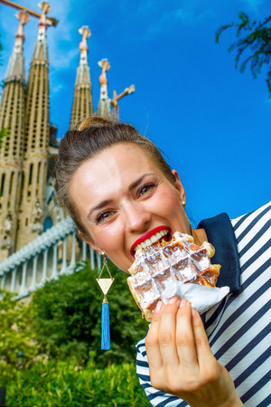 Foto de Barcelona - July, 10, 2017: elegant woman in stripy shirt near Sagrada Familia in Barcelona, Spain eating waffle - Imagen libre de derechos
