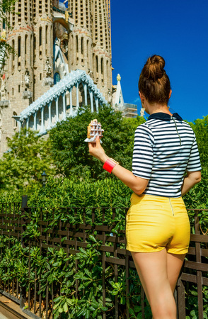 Foto de Barcelona - July, 10, 2017: Seen from behind young woman in yellow shorts and stripy shirt near Sagrada Familia in Barcelona, Spain with waffle - Imagen libre de derechos