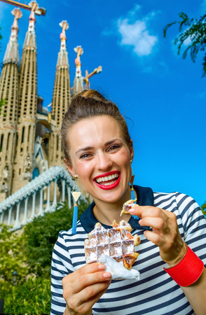 Foto de Barcelona - July, 10, 2017: Portrait of trendy woman in stripy shirt in the front of Sagrada Familia in Barcelona, Spain eating waffle - Imagen libre de derechos