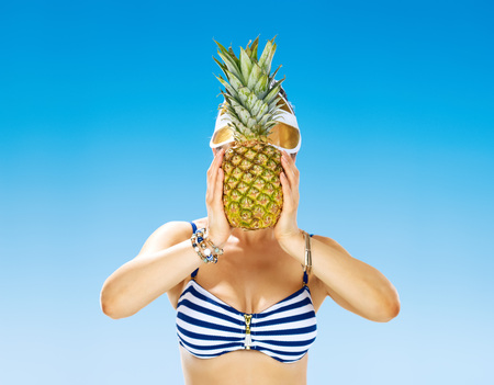 Photo for Perfect summer. young woman in swimsuit on the seacoast holding pineapple in the front of face - Royalty Free Image