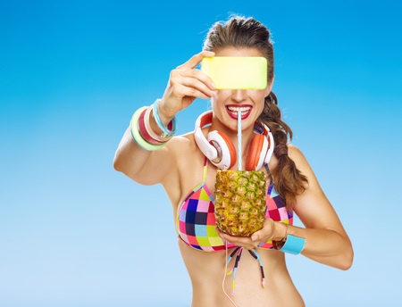 Photo for Perfect summer. happy healthy woman with headphones and wearing colorful swimsuit on the beach with refresh summer cocktail in pineapple with digital camera taking photo - Royalty Free Image
