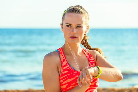 Foto de Refreshing wild sea side workout. young fit woman in sportswear on the seacoast setting fitness bracelet - Imagen libre de derechos
