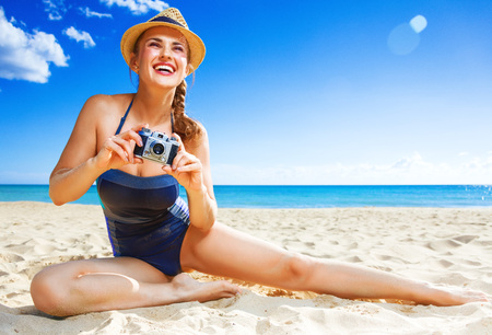 Photo for Sun kissed beauty. happy active woman in swimsuit on the seashore with digital camera taking photo - Royalty Free Image