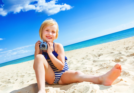 Photo for Sun kissed beauty. happy healthy girl in swimwear on the seacoast with retro photo camera - Royalty Free Image