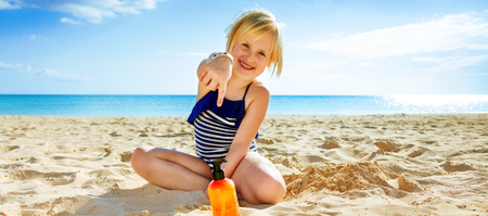 Photo for Sun kissed beauty. happy healthy child in swimwear on the beach  pointing at sun screen - Royalty Free Image