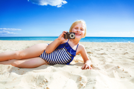 Photo for Sun kissed beauty. smiling healthy child in beachwear on the seacoast with digital camera taking photo - Royalty Free Image