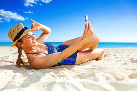 Photo for Sun kissed beauty. happy active woman in swimwear on the seacoast with mobile phone taking selfie - Royalty Free Image