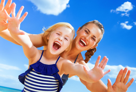 Photo for Sun kissed beauty. Portrait of cheerful young mother and child in swimsuit on the seashore having fun time - Royalty Free Image