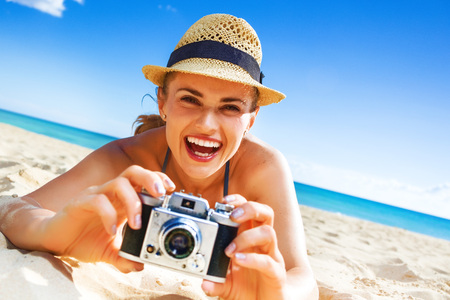 Photo for Sun kissed beauty. happy healthy woman in beachwear on the beach with digital camera taking photo - Royalty Free Image