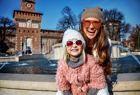Foto de Rediscovering things everybody love in Milan. Portrait of happy modern mother and daughter tourists in sunglasses near Sforza Castle in Milan, Italy - Imagen libre de derechos