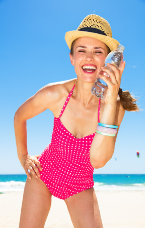 Photo for Portrait of happy young woman in colorful red swimsuit on the beach enjoying cold water - Royalty Free Image