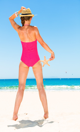 Photo for Seen from behind young woman in colorful red swimsuit on the beach with starfish looking into the distance - Royalty Free Image