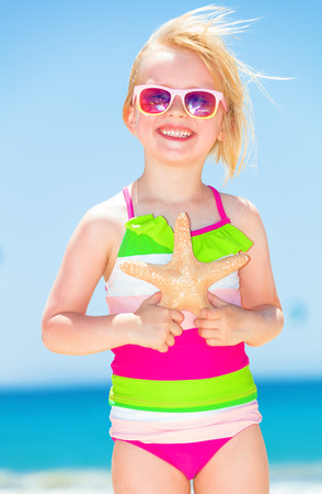 Photo for Portrait of happy modern child in colorful beachwear on the seacoast with starfish - Royalty Free Image