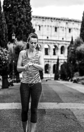 Foto de young woman jogger in sportswear in Rome, Italy using fitness bracelet - Imagen libre de derechos